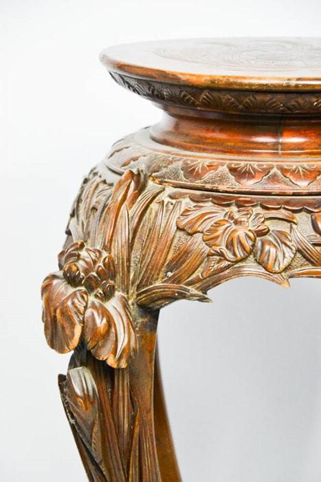 Lot 363 - A Chinese hardwood jardiniere stand, carved with protruding flowers to the top of the legs. Height