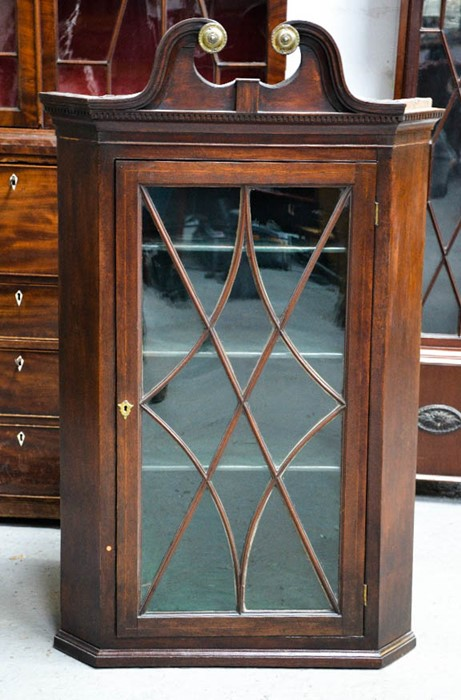 Lot 367 - A 19th century mahogany corner cupboard with split swan neck pediment and astrigal glazed door,