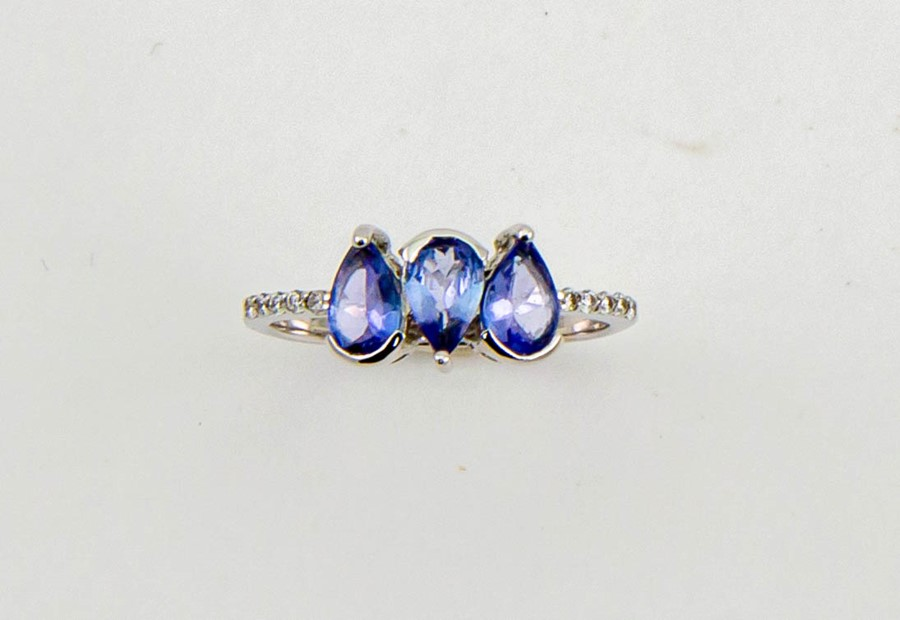 Lot 10 - An 18ct white gold, diamond and tanzanite ring, the three pear cut tanzanites totalling 1.50ct, with