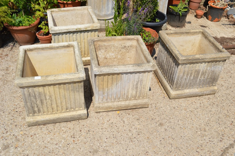 Lot 345 - A set of four stone planters, square form, classical fluted style, 44cm high, 46cm square.