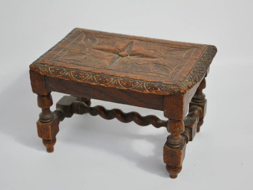 Lot 343 - A small 19th century oak stool, with lunette carved edge and flowerhead to the centre, raised on