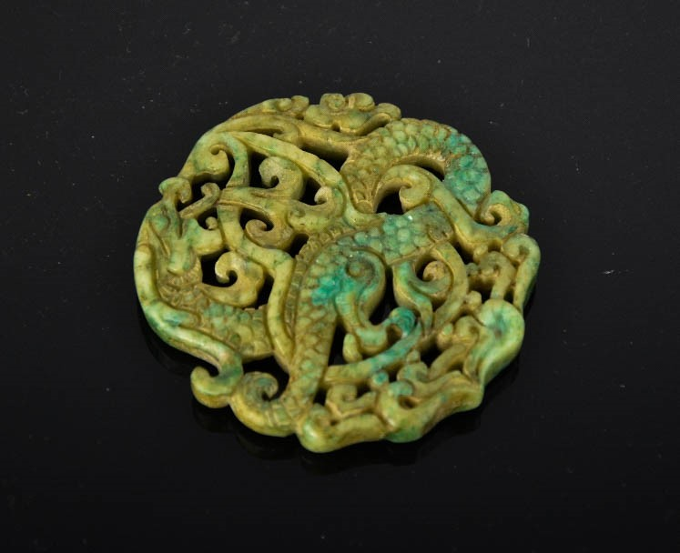 Lot 277 - A Chinese natural green jade hand carved pierce-work dragon pendant. 6.5cm by 6.5cm
