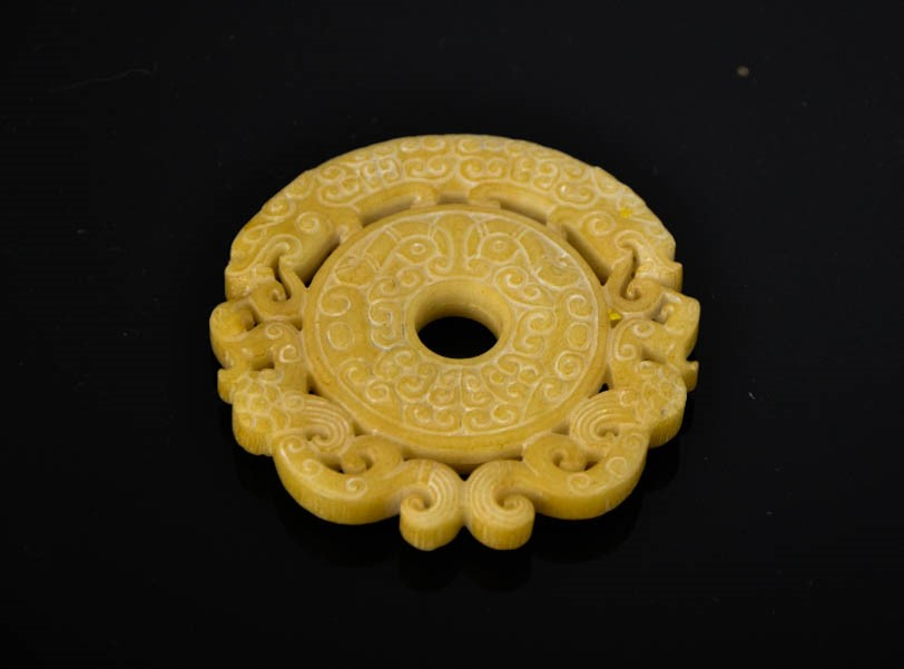 Lot 275 - A Chinese natural pale yellow jade hand carved dragon pendant. 7.5cm wide