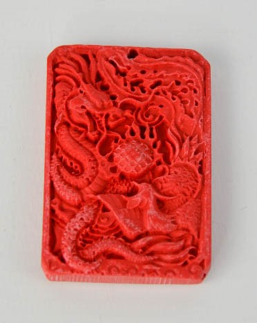Lot 251 - A Chinese carved cinnebar dragon pendant