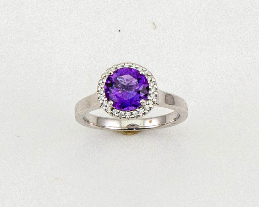 Lot 3 - An 18ct gold, amethyst and diamond ring, the brilliant cut amethyst 1.52ct, the bordering diamonds
