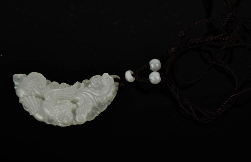 Lot 259 - A Chinese natural white jade half-moon carved floral pendant with cord and jade beads