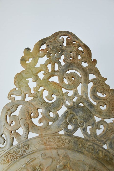Lot 246 - A Chinese hand carved natural jade plaque of dragons and phoenix design, with figures on horse and