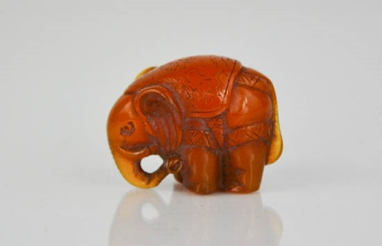 Lot 234 - An amber netsuke bead in the form of an elephant, carved with detail, 3cm high.