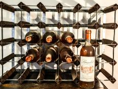 Eight bottles of Bandol 1980 rose wine, in a wine rack.