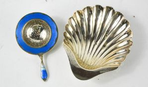 A silver scallop form dish, together with an enamel and white metal tea strainer, marked 925,