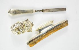 A white metal rattle in the form of a dog, a silver handled nail buff and file.