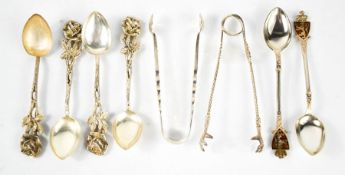 A group of silver and white metal spoons, a silver pair of sugar tongs, and a Mappin & Webb pair