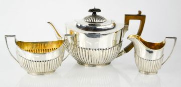 A Victorian silver three piece tea set, of oval form with gadrooned lower body, comprising teapot,
