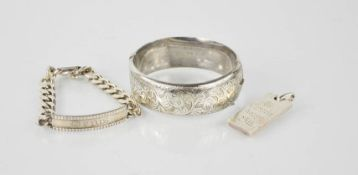 Four pieces of silver: an ingot, a silver bangle engraved with chased design, a chain link