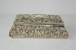 A Victorian silver dressing table box by William Comyns & Sons, embossed with scrollwork, flowers