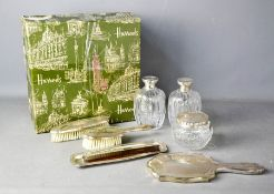 An eight piece white metal dressing table set, comprising pair of cut glass flagons, powder bowl,