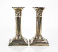 A pair of silver corinthian column form candlesticks, Birmingham 1905, 14cm high.