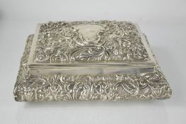 A silver rectangular dressing table box, London 1905 by William Comyns, embossed with scrollwork,
