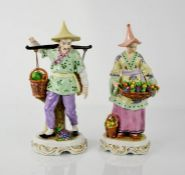 A pair of 19th century Sitzendorf oriental figures carrying baskets of fruit, 24cm high.
