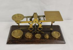 Set of brass postal scales with weights to 16oz, plinth base, 32cms wide
