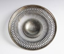 A white metal dish, of circular form with pierced decoration border on pedestal foot, with