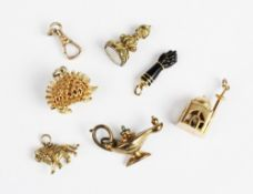 A selection of gold and yellow metal bracelet charms, to include a gold mounted jet coloured figa