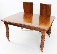 An early 20th century golden oak extending dining table, the rectangular top with moulded and