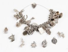 A silver charm bracelet with assorted silver and white metal charms,