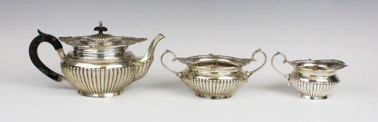 A Victorian three-piece silver tea service by Walker & Hall, Sheffield 1899, comprising teapot, milk