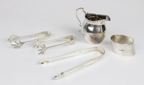 An Edwardian silver cream jug by George Unite, Birmingham 1904, of plain polished baluster form with