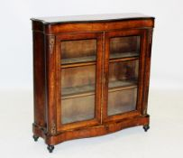 A late 19th century Louis XV style serpentine vitrine, the moulded top with an ebonised border above