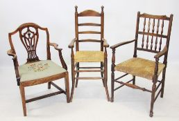 A 19th century oak spindle back elbow chair, with an envelope rush seat on turned legs and plain