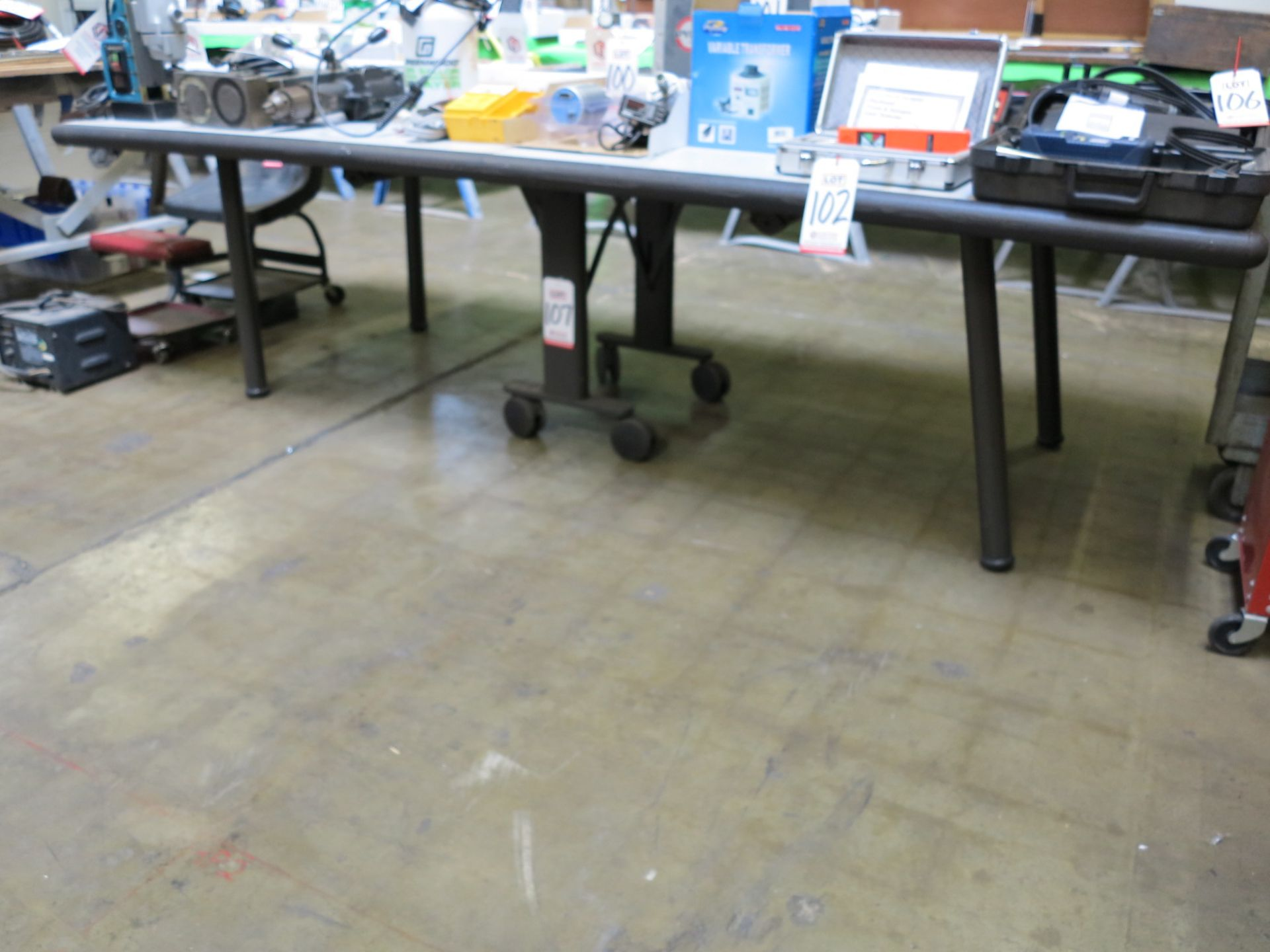 """Lot 107 - FOLDING TABLE W/ CASTERS, 9' X 42"""", TOP HAS SOME COSMETIC DAMAGE"""