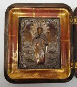 (Antiek) Russische ikoon St. Nicholas van Myra Russische ikoon met metalen riza, gemonteerd achter glas in houten box. St. Nicholas van Myra, 19e eeuw. Conditie: Kleine beschadigingen, zie foto's. Afmetingen: Lengte 20 cm, breedte 17,5 cm en hoogte 5,4 cm.