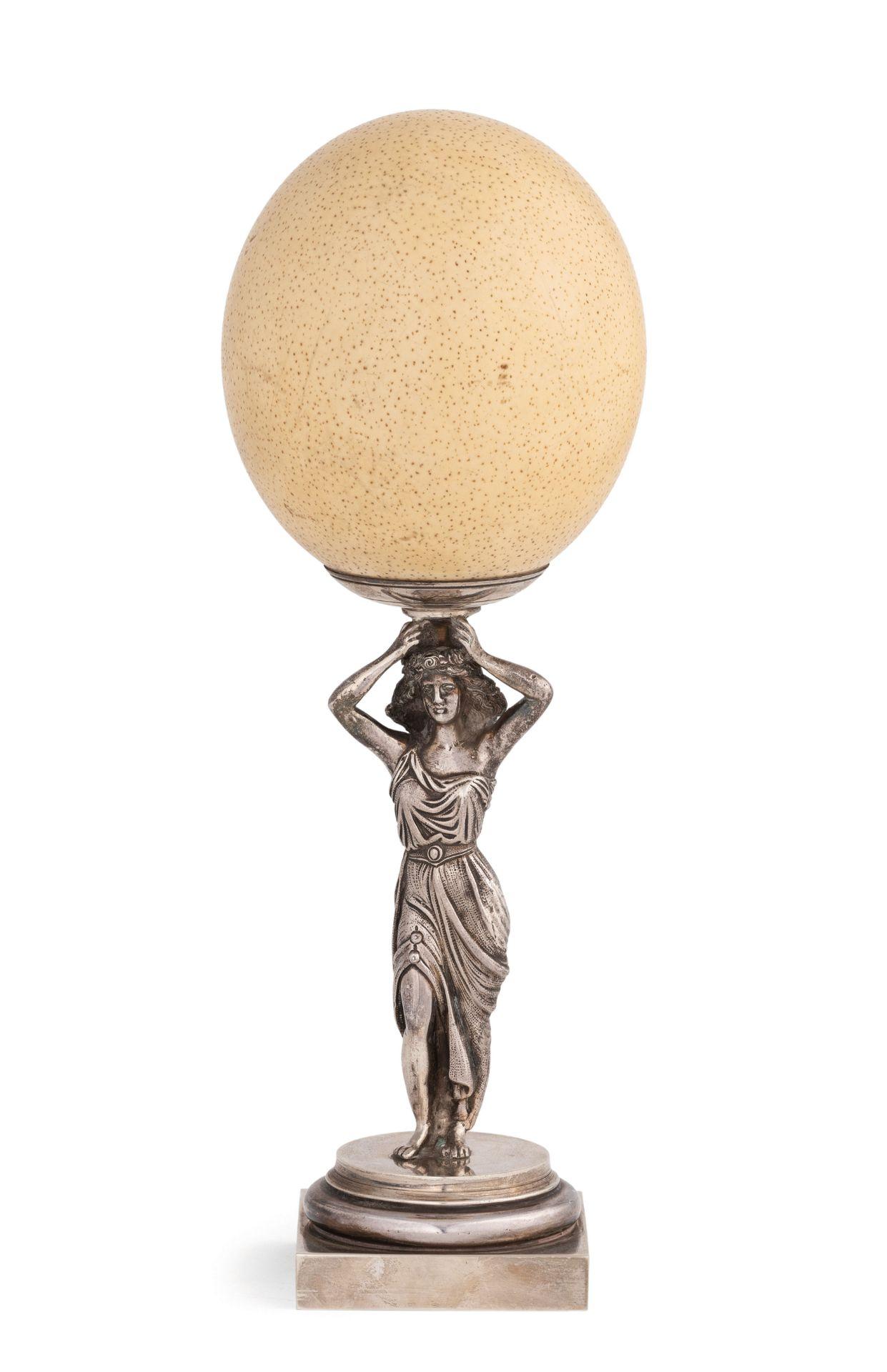 Los 1 - a base circolare su plinto, fusto a figura femminile a reggere un uovo; usureAlt. cm 34, larg. cm...