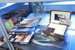Shelf of mixed items including DVDs, Kevin Platt framed print and a digital camera. Not available