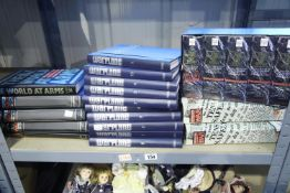 Shelf of binders of wartime images and war planes in binder folders and video cassettes of the world