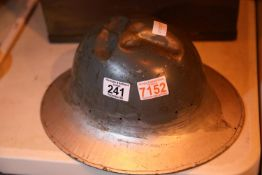 Military helmet of indeterminate age, showing possible battle damage. P&P Group 1 (£14+VAT for the