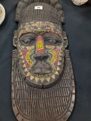 A 20th century carved, brass/beaded African wall hanging mask