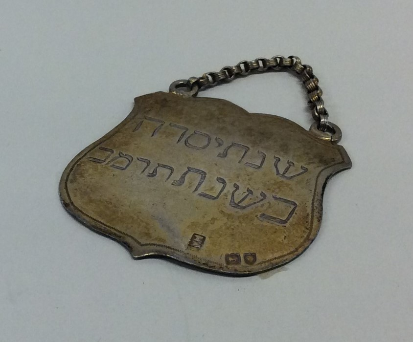 Lot 42 - A silver Hebrew shield shaped plaque with suspensi