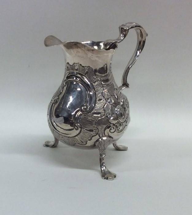 Lot 39 - A good Georgian silver helmet shaped cream jug emb
