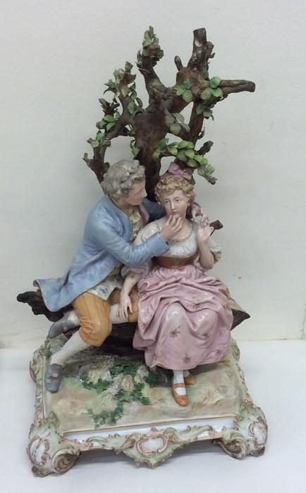 Lot 43 - A large porcelain figure of a romantic couple bene