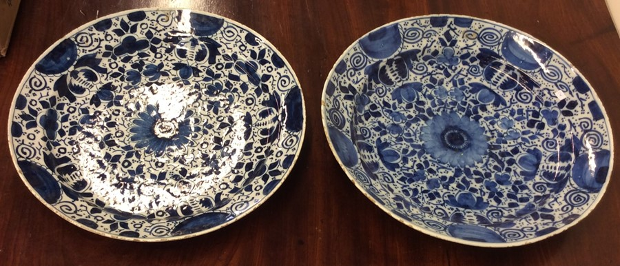 Lot 14 - Two large blue and white Delft chargers with flora