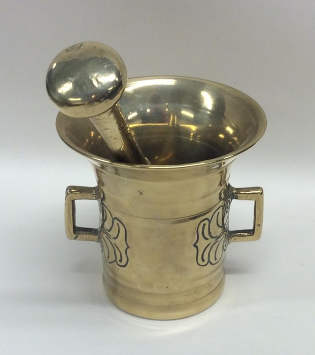 Lot 33 - A good Antique brass pestle and mortar decorated w