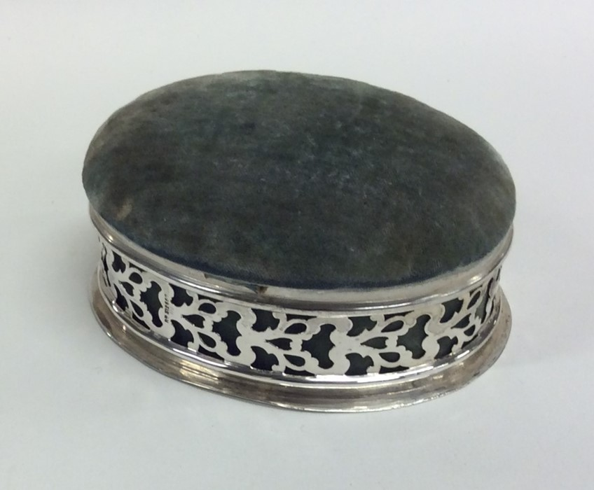Lot 22 - An oval silver pin cushion / jewellery box with sc