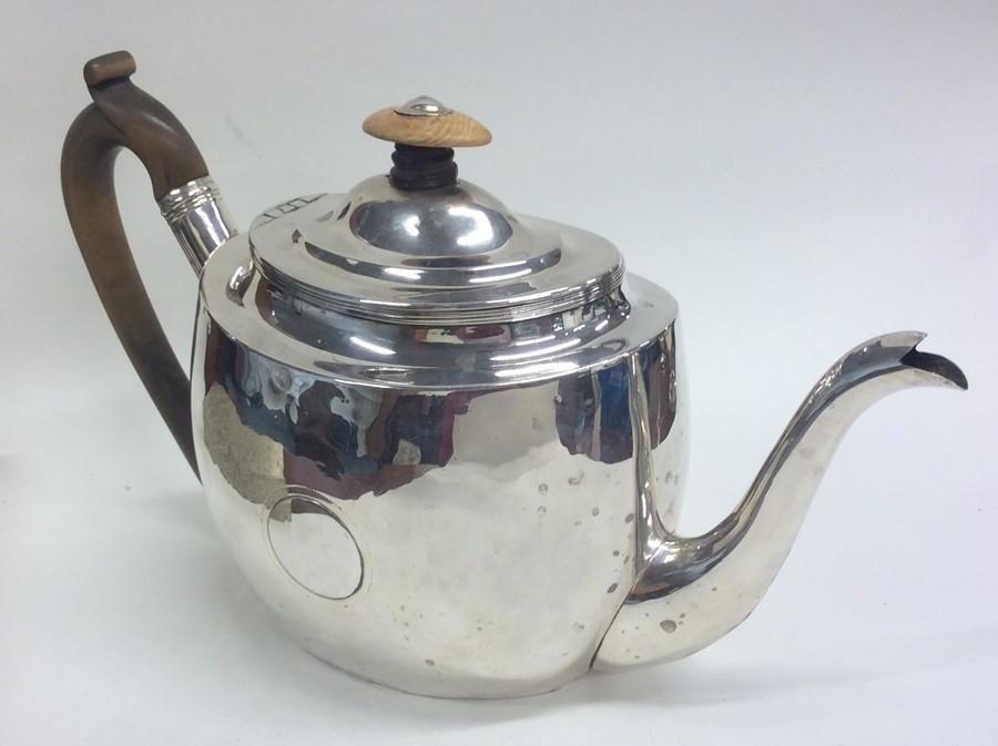 Lot 24 - A large plain oval Georgian silver teapot. London.