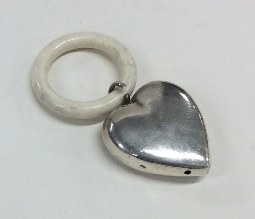 Lot 44 - An unusual silver heart shaped rattle / teether. A