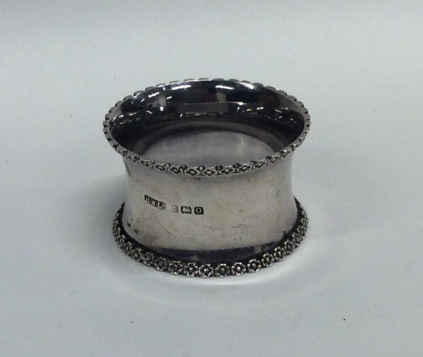 Lot 40 - A heavy silver napkin ring decorated with flowers