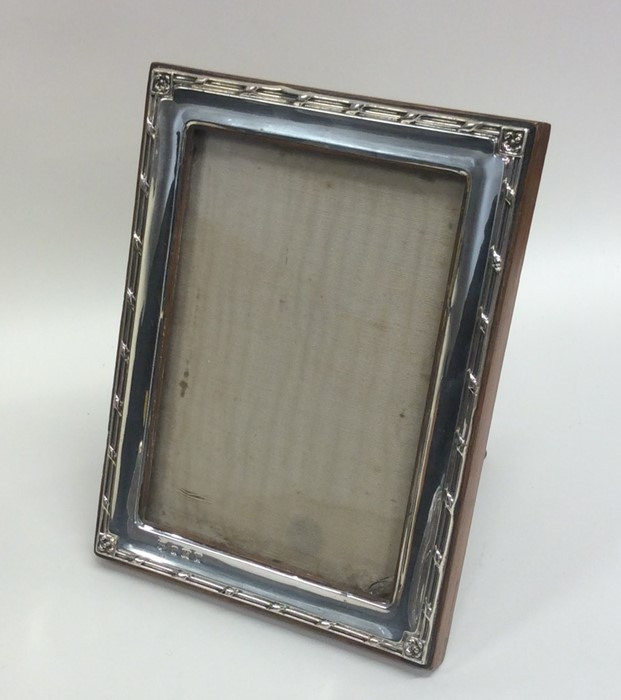 Lot 34 - A rectangular silver mounted picture frame on oak