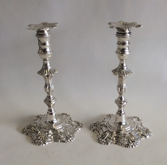 A good pair of cast silver taper candlesticks with